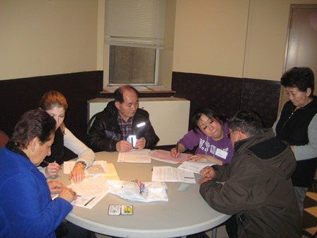 Jai, a Korean speaking social service worker, assists a group of Korean Serviam residents.