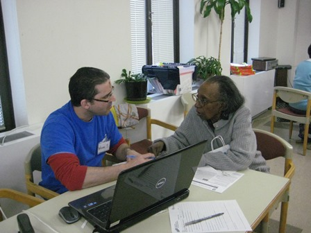 William finishes up Mildred's tax return in the community room of Rose Hill Apartments.