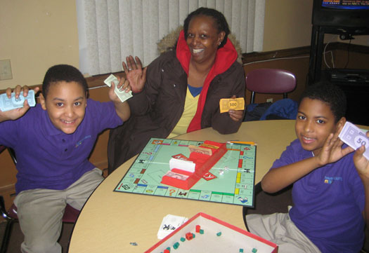 Patricia waits with her grandsons and enjoys some Monopoly.